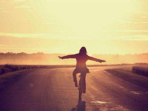 Kvinna cyklar på väg och känner sig lycklig