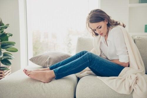 Kvinna som har magont i soffan.