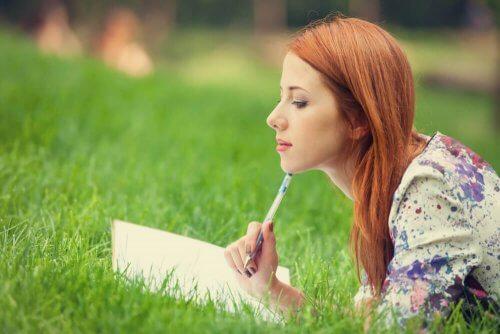 Kvinna som ligger och skriver i gräset.