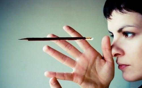 Kvinna som tittar på en penna.