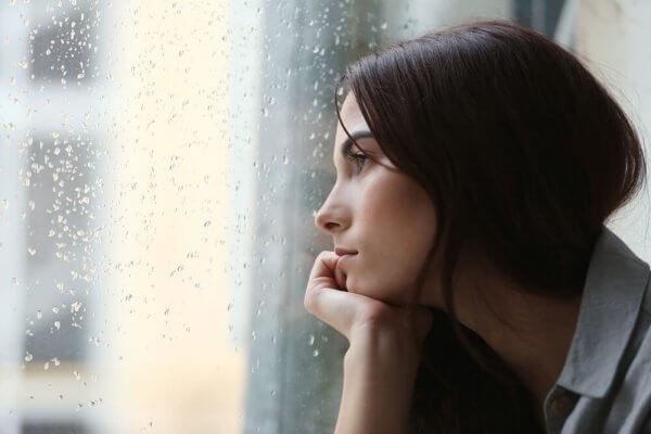 Nedstämd kvinna tittar ut genom regnigt fönster