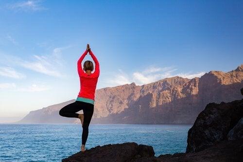 Kvinna som gör yogaställningen Vrikasana