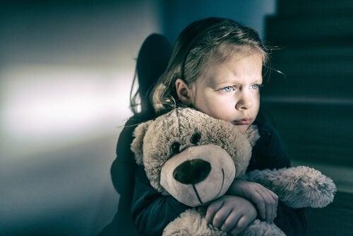 Ledsen flicka som kramar sin nallebjörn