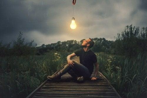 Man som sitter under tänd glödlampa