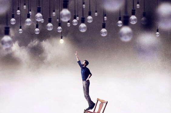 Man på stol sträcker sig efter glödlampor