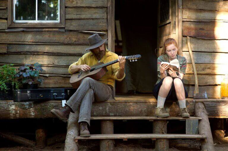 Man som spelar gitarr bredvid sin dotter.
