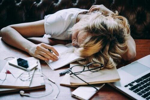 Trött kvinna med huvudet på skrivbordet
