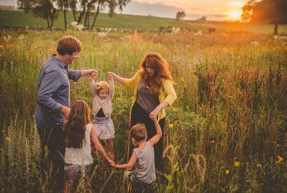 Familj som dansar på en äng.