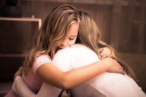 Flicka som kramar sin mamma.
