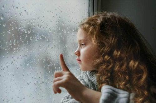 Flicka som ser ut genom fönster i regn