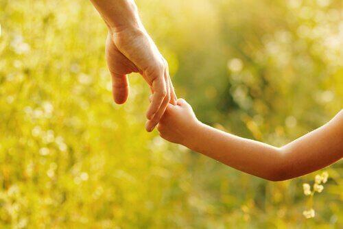 Förälder som håller barn i handen.
