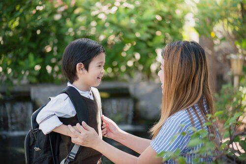 Glad pojke som har på sig ryggsäck.