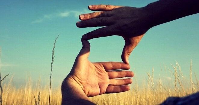 Händer som ramar in ett fält.