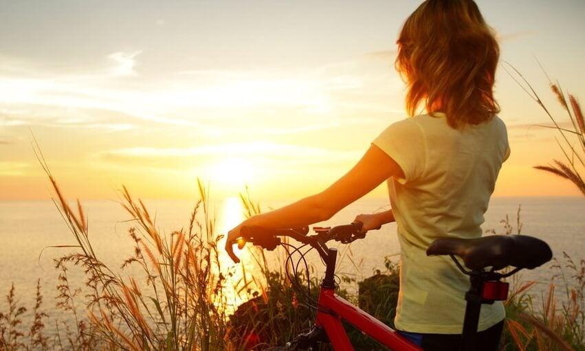Kvinna med cykel framför havet.