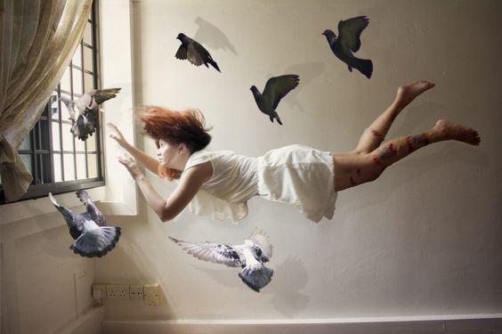 Kvinna som flyger bland duvor.