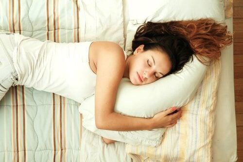 Kvinna som håller om sin kudde.