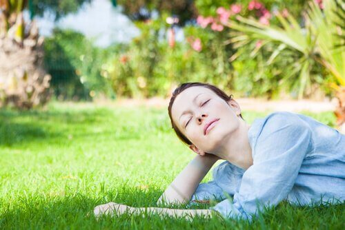 Kvinna som ligger i gräset.