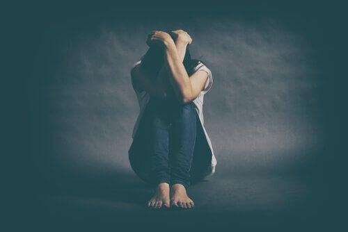 Kvinna som sitter ner och är deprimerad.