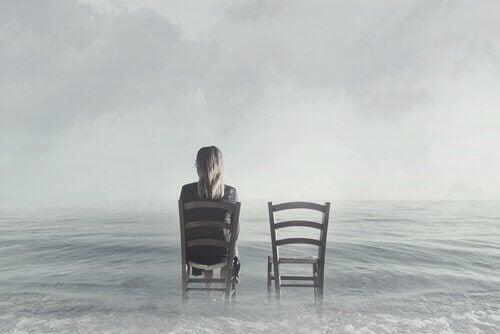 Kvinna som sitter på en stol i havet.