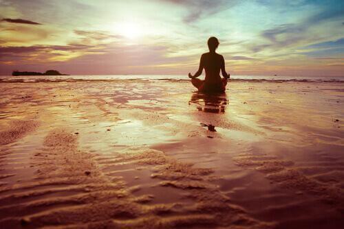 Kvinna som sitter vid havet och mediterar.