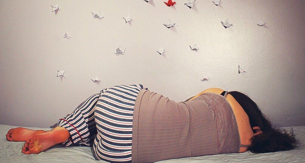 Kvinna som sover på sängen.