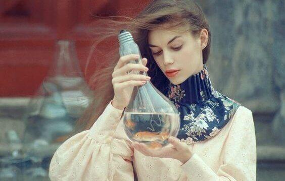 Kvinna som tittar på guldfisk.