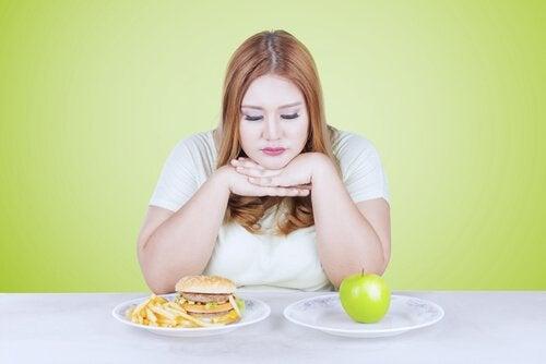 Kvinna som väljer mellan skräpmat och äpple.