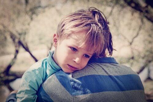Ledsen pojke som blir kramad