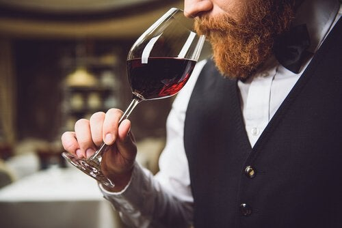 Man med skägg som luktar på vin.