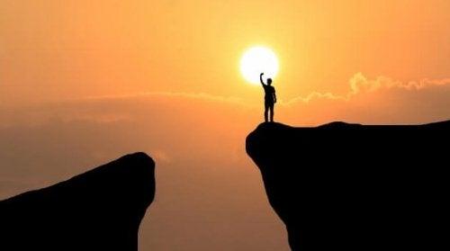 Man på en klippa vid solnedgången