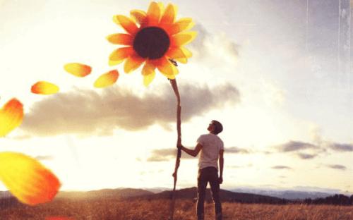 Man som håller i en solros.