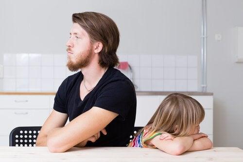Pappa och dotter med ryggen mot varandra