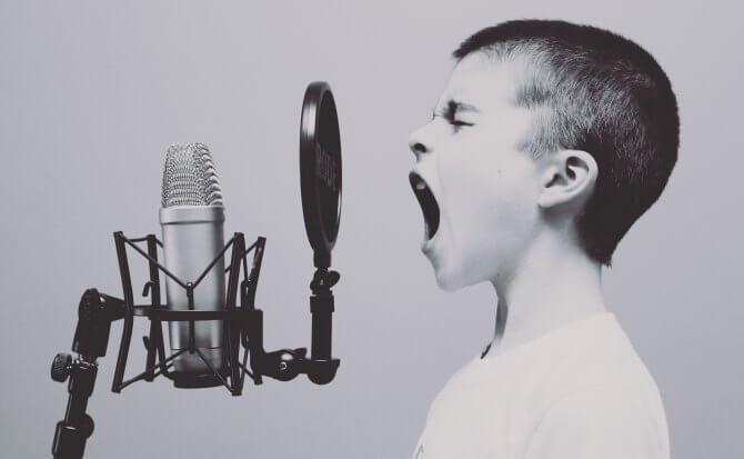 Pojke som pratar i mikrofon.