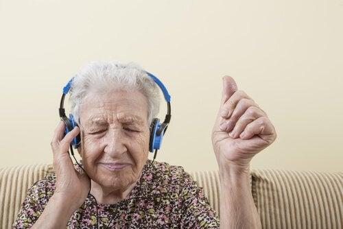 En äldre kvinna med hörlurar