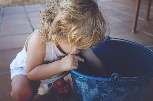 En liten flicka som utforskar en hink