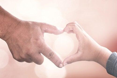 Far och son som bildar hjärta med händerna