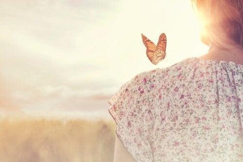 Fjäril som landar på en kvinnas axel.