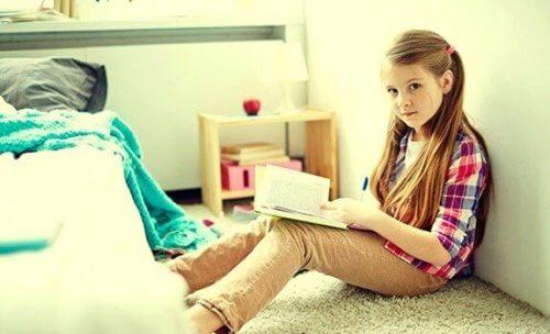 Flicka läser i sitt rum