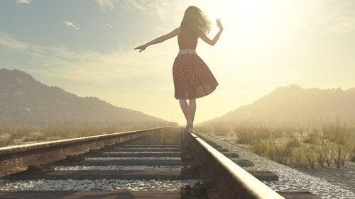 Kvinna som går på järnväg.