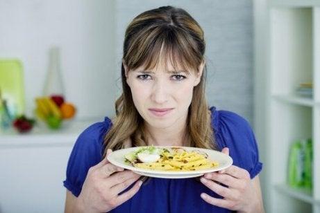 Kvinna som håller upp tallrik med mat.