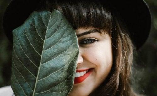 Kvinna som ler bakom ett löv.