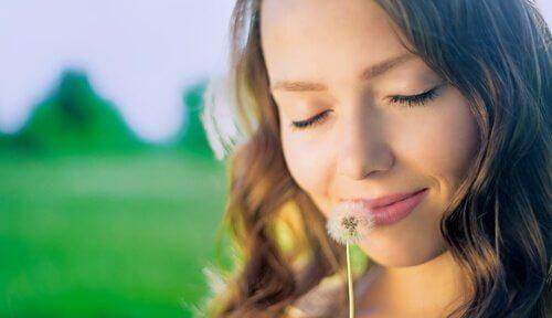 Kvinna som luktar på maskros.