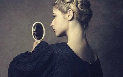 Kvinna som ser sig själv i spegeln