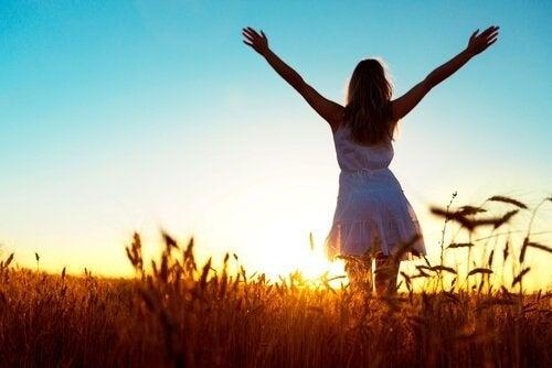En lycklig kvinna med öppna armar vid solnedgången