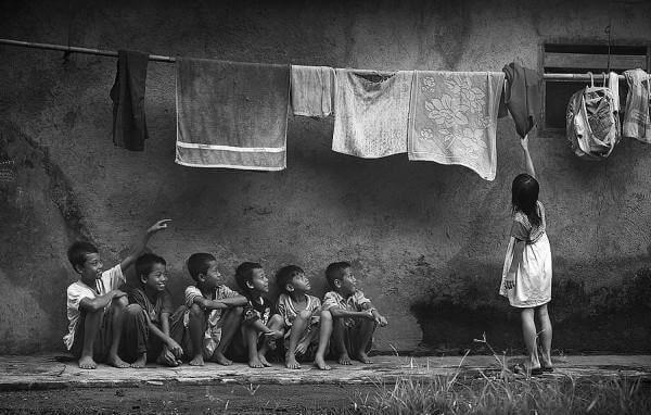 Pojkar tittar på flicka som hänger tvätt