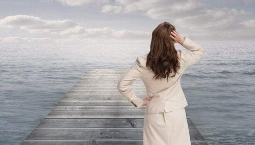 Förvirrad kvinna som står på brygga