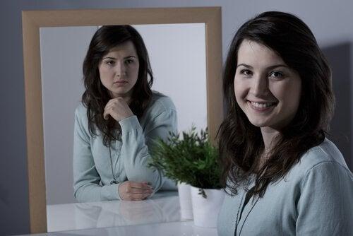 Leende kvinna som ser ledsen ut i spegeln