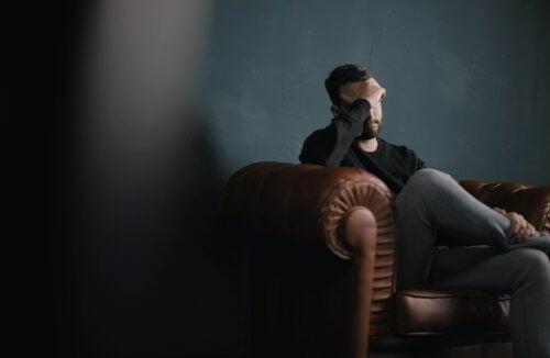 Man med sömnproblem som sitter i soffan
