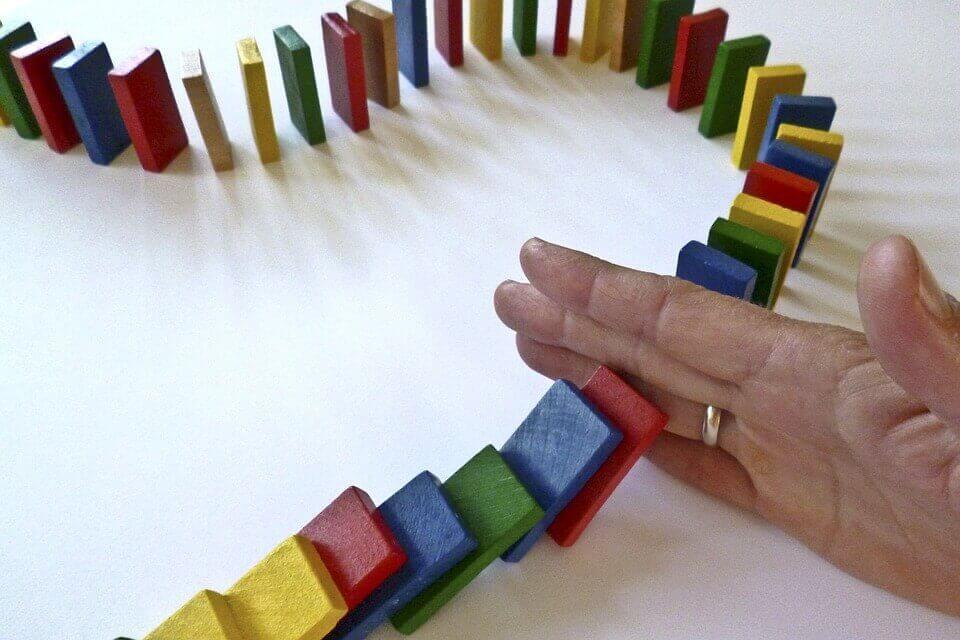 hand som stoppar domino