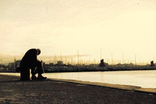 En sorgsen gammal man sitter själv framför en sjö.